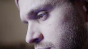 Gesicht des jungen kaukasischen, bärtigen, braunen gemusterten ernsten Mannes im Tageslichtraum stock video footage