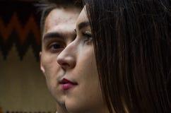 Gesicht des jungen schönen Mädchens, das den Abstand auf dem Hintergrundgesicht des jungen Kerls, ein Paar in der Liebe untersuch Stockfoto