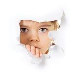 Gesicht des Kindes, das durch ein Loch im Papier schaut Lizenzfreie Stockbilder