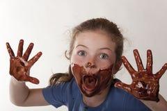 Gesicht des kleinen Mädchens abgedeckt in der Schokolade Stockbild