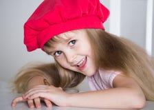 Gesicht des kleinen Mädchens, roter Hut, Spaß, Abschluss oben Lizenzfreie Stockfotos
