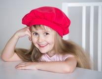 Gesicht des kleinen Mädchens, roter Hut, Spaß, Abschluss oben Lizenzfreie Stockfotografie