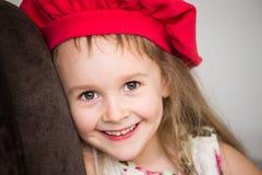 Gesicht des kleinen Mädchens, roter Hut, Spaß, Abschluss oben Lizenzfreies Stockbild