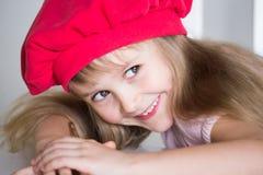 Gesicht des kleinen Mädchens, roter Hut, Spaß, Abschluss oben Stockfotos