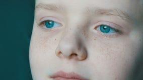 Gesicht des schönen Jugendlichen mit Sommersprossegroßaufnahme Ein Junge mit ungewöhnlichem Türkis mustert das Schauen in den Abs stock video