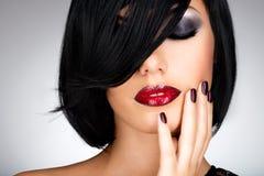 Gesicht einer Frau mit schönen dunklen Nägeln und den sexy roten Lippen Lizenzfreie Stockbilder