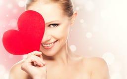 Gesicht einer schönen jungen Frau mit rotem Herzen Stockbild