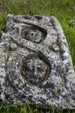 Gesicht graviert im Teil des keltischen Kreuzes legend auf dem Boden Stockbilder