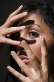 Gesicht hinter Fingern Stockfotografie