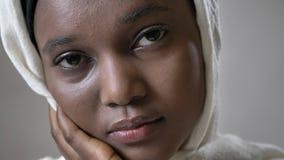 Gesicht ofoung trauriges afrikanisches moslemisches Mädchen im hijab passt an der Kamera, religioun Konzept, grauer Hintergrund a stock video