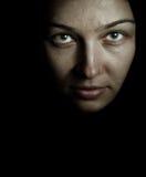 Gesicht und Augen der gespenstischen Geheimnisfrau in der Dunkelheit Lizenzfreie Stockfotografie