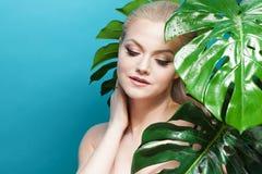 Gesicht von attraktivem jungem blondem und Blätter von Palmen Junge Frau im blauen Bikini auf blauem Hintergrund Lizenzfreie Stockbilder