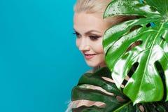 Gesicht von attraktivem jungem blondem und Blätter von Palmen Junge Frau im blauen Bikini auf blauem Hintergrund Stockfoto