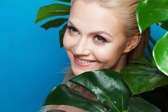 Gesicht von attraktivem jungem blondem und Blätter von Palmen Junge Frau im blauen Bikini auf blauem Hintergrund Lizenzfreies Stockfoto
