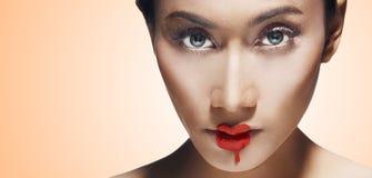 Gesichts-hübsche Frauen mit Lippenstift schmelzen auf ihren Lippen Stockbild