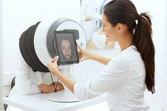 Gesichts-Haut-Analyse Frau am Cosmetology, der Haut-Diagnose tut stockfotos