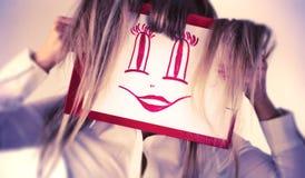 Gesichtsabbildung der Holding der jungen Frau lächelnde Stockfotos