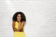Gesichtsausdrücke der jungen schwarzen Frau auf Backsteinmauer Stockfotos