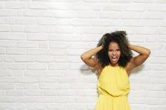 Gesichtsausdrücke der jungen schwarzen Frau auf Backsteinmauer Lizenzfreies Stockfoto