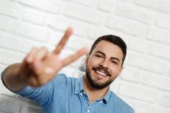 Gesichtsausdrücke des jungen Bart-Mannes auf Backsteinmauer Stockbilder