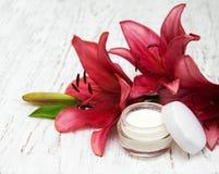 Gesichtscreme mit Lilienblumen Stockfotos