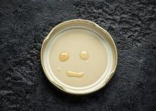Gesichtslächeln gemacht mit Honigtropfen auf Deckel stockbilder