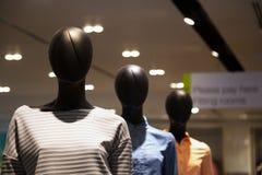 3 gesichtslose schwarze weibliche Plastikmannequins in Folge am Einkaufszentrum Lizenzfreie Stockfotos