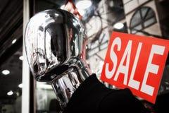 Gesichtslose silberne Mannequinkopfnahaufnahme Rotes Verkaufszeichen stockfotos