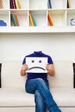 Gesichtsloser Mann, der auf Sofa sitzt Lizenzfreie Stockfotos