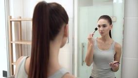 Gesichtsmake-up Frau, die Pulver verwendet und im Spiegel schaut stock video