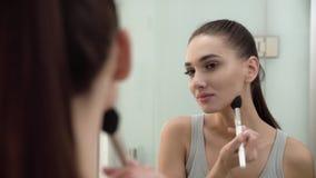 Gesichtsmake-up Frau, die Pulver verwendet und im Spiegel schaut stock video footage