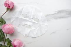 Gesichtsmaske und Rosen als Symbol der Schönheit und Sorgfalt des Körpers stockfotografie