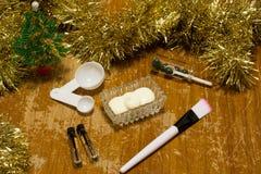 Gesichtsmasken auf einem hölzernen Hintergrund mit Weihnachtsbällen Lizenzfreies Stockfoto