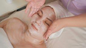 Gesichtsmassage einer Asiatin von mittlerem Alter in einem Schönheitssalon Der Kosmetiker überträgt die Hitze der Hände, ohne das stock video