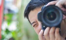 Gesichtsnahaufnahme des männlichen Fotografen Fotos machend Stockfotografie