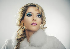Gesichtsporträt eines schönen Mädchens in einem weißen Mantel Stockfotografie