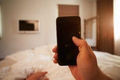 Gesichtspunkt-Bild von Person In Bed Looking At-Handy stockfoto
