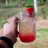 Gesichtspunkt einer Hand der manÂs, die ein Glasgefäß mit einem kalten roten Getränk hält lizenzfreies stockfoto
