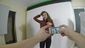 Gesichtspunkt eines jungen Fotografen, der Fotos ihrer vorbildlichen Freundin mit einem intelligenten Telefon macht stock footage