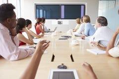 Gesichtspunkt geschossen von den Wirtschaftlern um Sitzungssaal-Tabelle lizenzfreie stockfotos