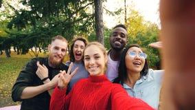 Gesichtspunkt schoss vom Holdinggerät der jungen Frau mit Kamera und Nehmen selfie mit multiethnischer Gruppe der Freunde im Park lizenzfreies stockfoto