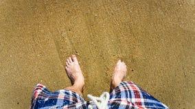 Gesichtspunkt schoss von einem Mann, der im Sand auf einem Strand steht lizenzfreie stockfotografie