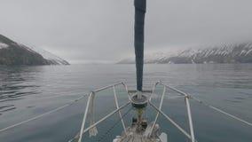 Gesichtspunkt von der Bogenseeyacht, die schneebedeckte Insel schwimmt und Berge gestalten landschaftlich stock footage