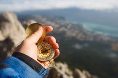 Gesichtspunktfoto des Forschermannes Richtung mit goldenem Kompass in seiner Hand über Wolken mit Herbst suchend Stockfotos