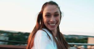 Gesichtspunktschuß des Jungen, der dem attraktiven jungen netten Mädchen mit dem schönen Lächeln um spinnt folgt stock footage