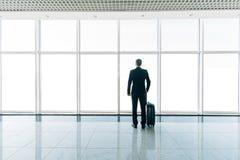 Gesilhouetteerd achtermeningsbeeld van zakenman met bagage die door venster luchthaven bekijken royalty-vrije stock afbeeldingen