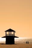 Gesilhouetteerd paar dat langs strand bij zonsondergang loopt Royalty-vrije Stock Afbeelding