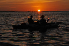 Gesilhouetteerd paar in kajak bij zonsondergang met wijn Royalty-vrije Stock Afbeeldingen