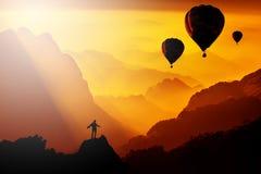 Gesilhouetteerd van de mens die zich op berg met luchtballonnenfl bevinden Stock Foto's