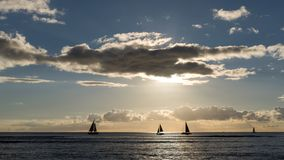 Gesilhouetteerde drijvende varende boten bij de zonsondergang bij Waikiki-strand, het eiland van Honolulu, Oahu, Hawaï, de V.S. royalty-vrije stock afbeelding